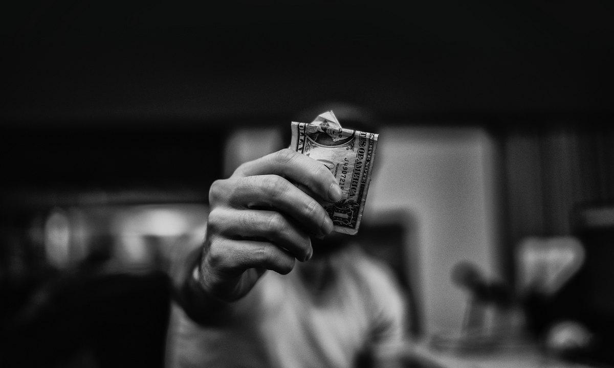 держит деньги в руках