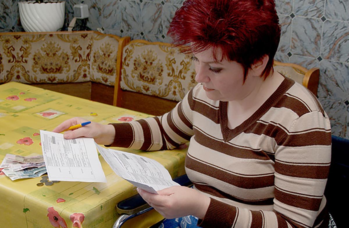 Женщина рассматривает счета за квартиру