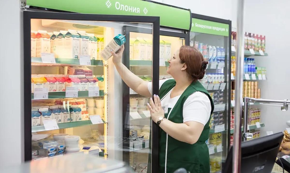 Женина достает молочные продукты из холодильника в магазине