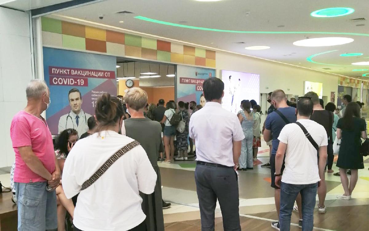 Люди стоят в очереди за вакциной