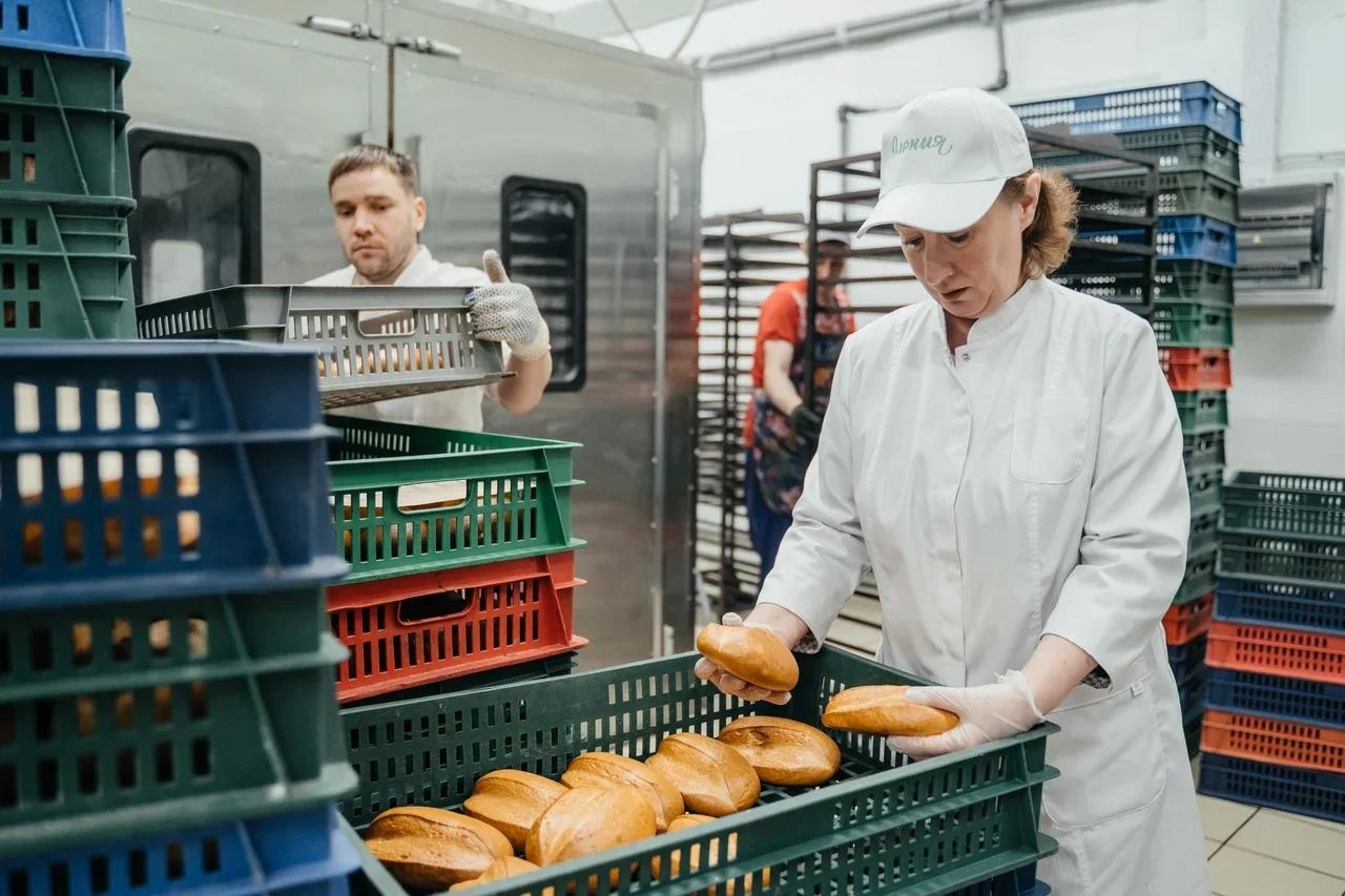 Женщина раскладывает булки в пекарне