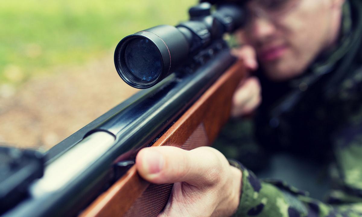 мужчина стреляет из ружья